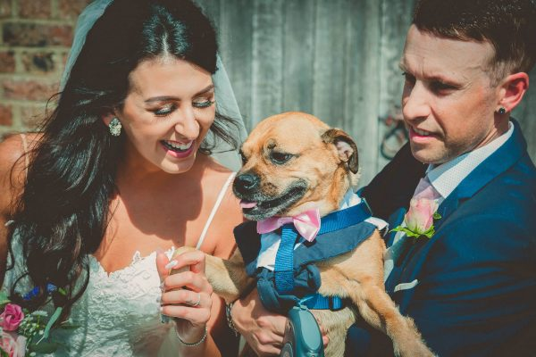 Bride and groom smile with their pet dog