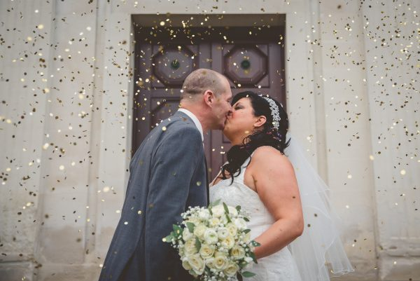 bride and groom kiss under confetti