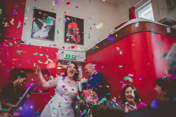 Bride and groom confetti entrance at a fun wedding in Brighton