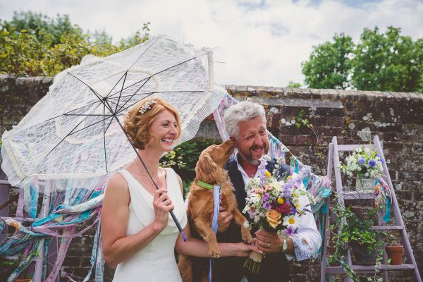 Bride and groom laugh as dog licks their faces