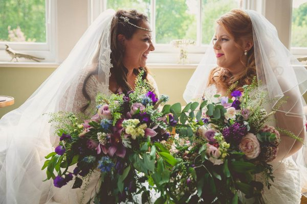 2 Brides looking at each other at a same sex wedding in sussex
