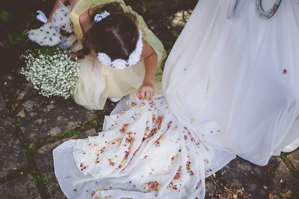 Flower girl picking up petals from bride's dress