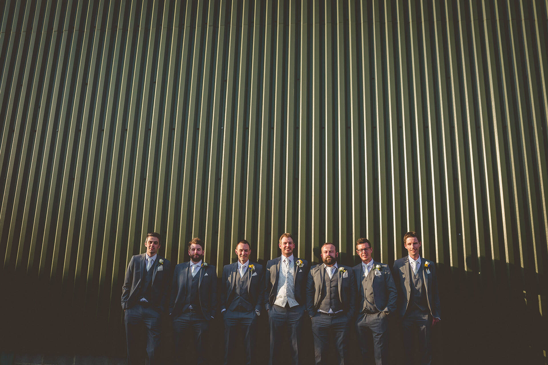 Groomsmen looking quirky in front of garage door