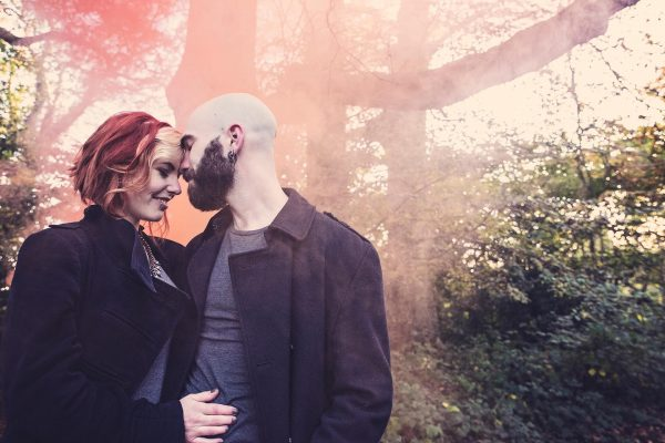 Couple kiss in front of a smoke bomb