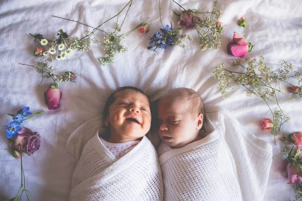 Twins on bed surrounded by flowers
