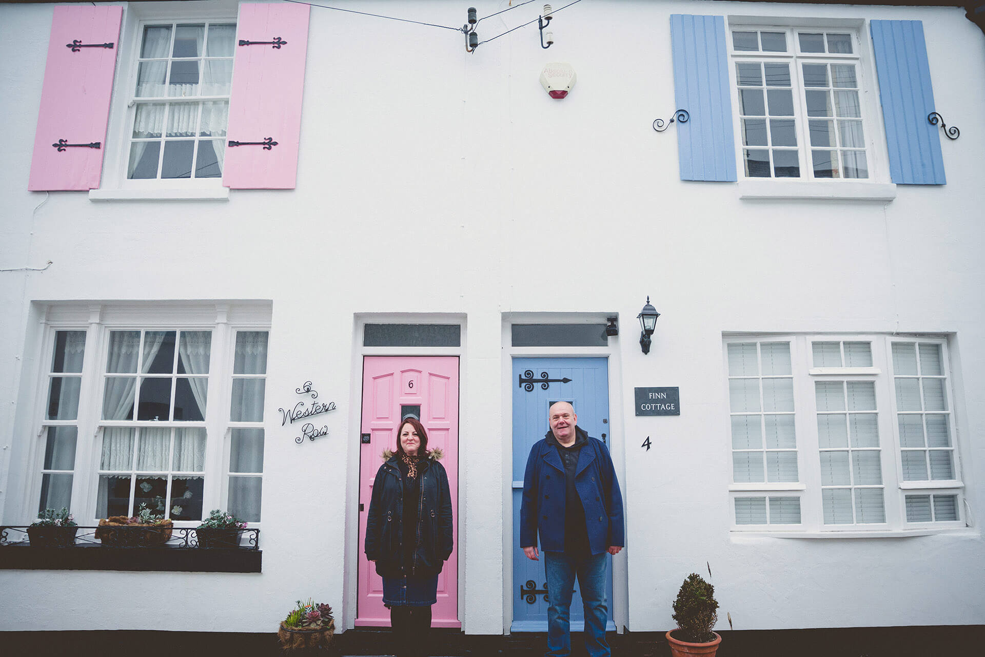 Couple pose in front of coloured doors