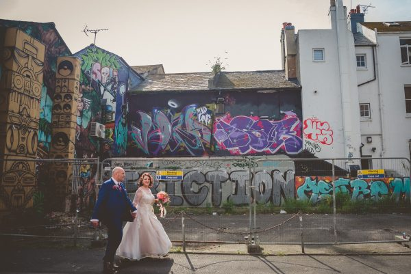 Bride and groom walk in front of graffity wall in Brighton
