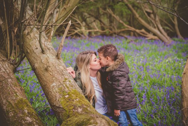 Mother and boy kiss in the bluebell woods