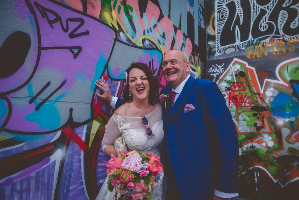 Bride and groom laugh in front of graffity wall