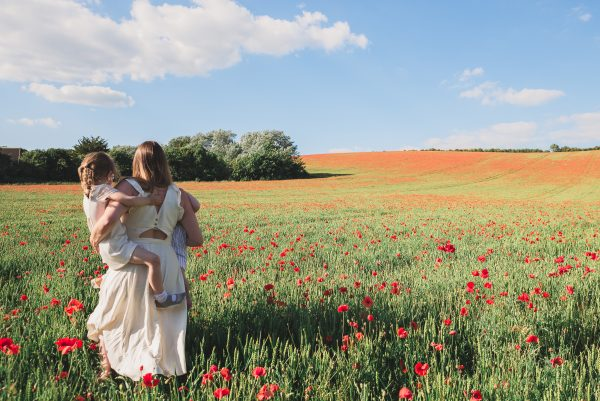 Mum and kids walking through poppy field