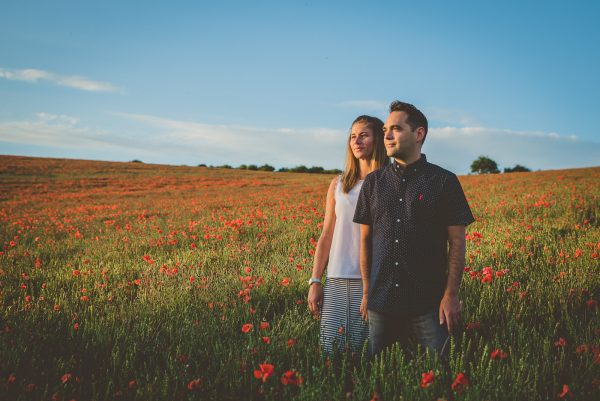 Couple hold hands in a poppy field