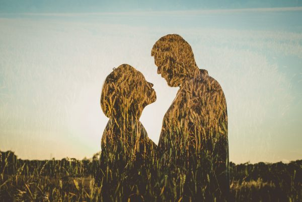 couple looking at each other blending with a field of wheat