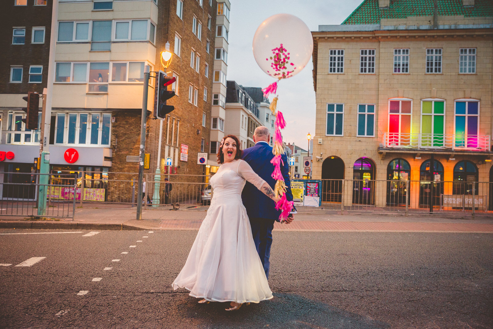 Couple crossing brighton road on their wedding day