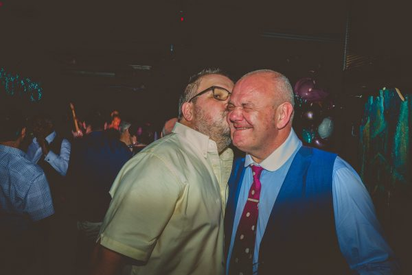 Groom being kissed by a male guest