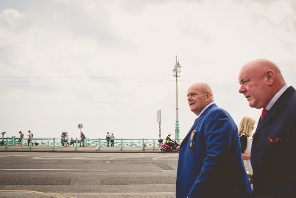 Groom and his friends walking on Brighton seafront on their way to the wedding