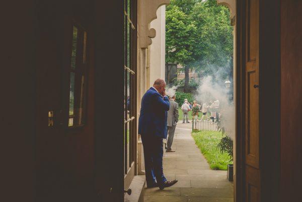 Groom smoking outside Pavilion