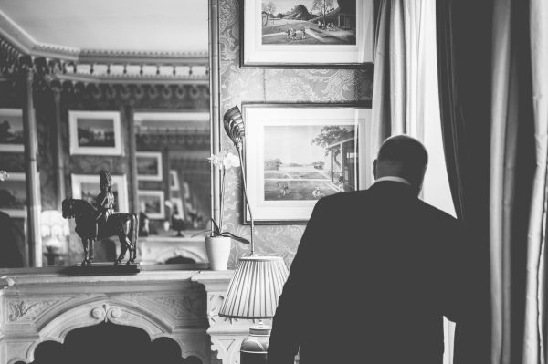 Wedding photographer captures Groom peeking out of the window waiting for bride at Brighton