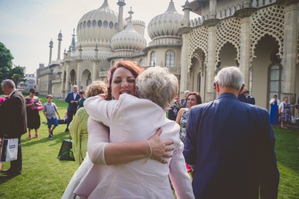Bride hugging guests outside brighton pavilion