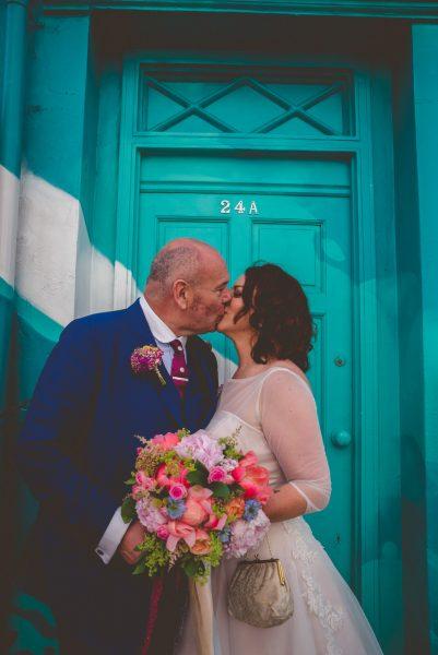 bride and groom kiss in front of bright door