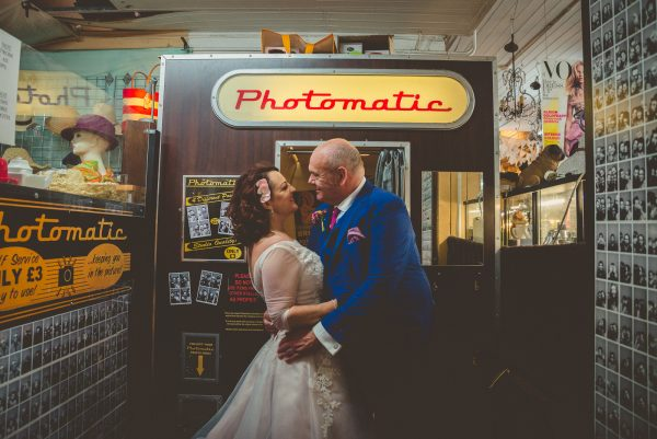 Bride and groom look at each other in front of photo booth