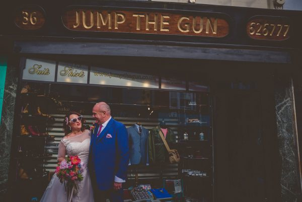 Bride and groom pose outside mod shop in Brighton