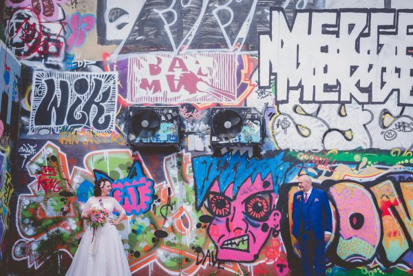 bride and groom pose in front of graffitti walls