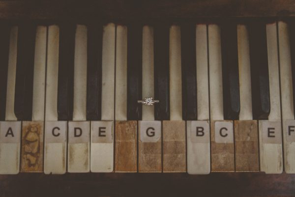 Close up of bride's engagement ring on piano keys