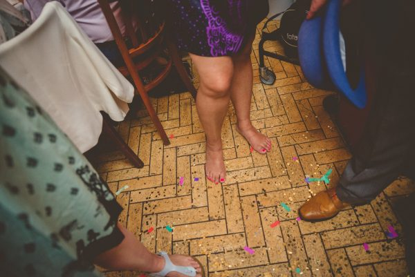 Confetti covered floor and wedding guests feet