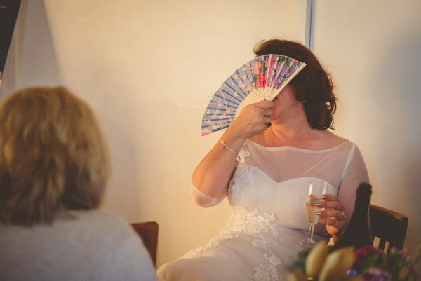 Bride covers face with a fan