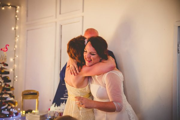 Maid of honour and bride hug