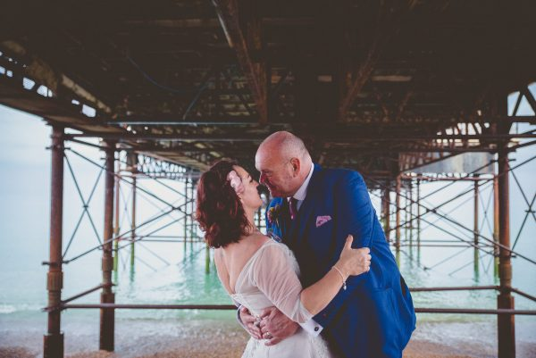couple kiss under brighton pier